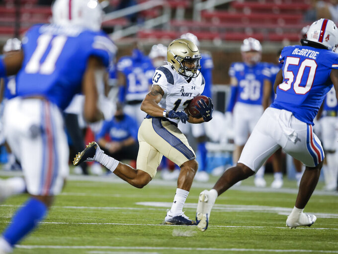 Navy running back Chance Warren (13) looks for room as SMU linebacker Richard McBryde (50) defends during the first half of an NCAA college football game, Saturday, Oct. 31, 2020, in Dallas. (AP Photo/Brandon Wade)