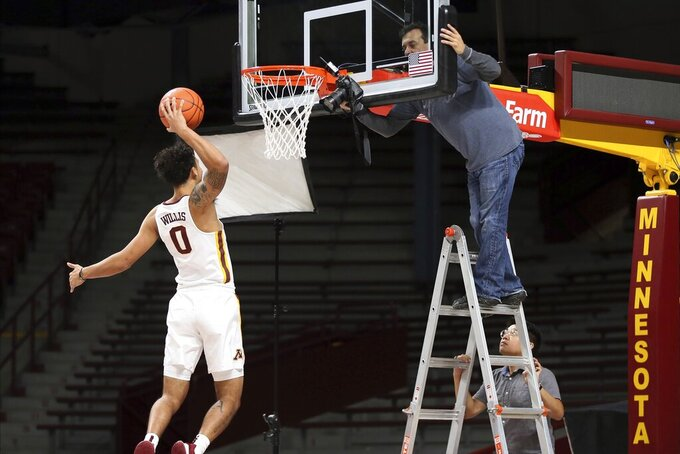 Minnesota's Payton Willis, left, jumps in a pose for photographer Carlos Gonzalez during NCAA college basketball media day Friday, Oct. 18, 2019, in Minneapolis. (AP Photo/Jim Mone)