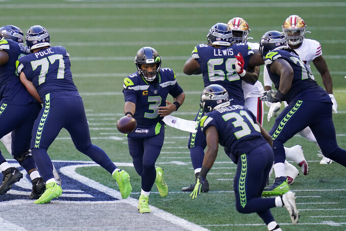 Seattle Seahawks quarterback Russell Wilson hands off to running back DeeJay Dallas (31) during the first half of an NFL football game against the San Francisco 49ers, Sunday, Nov. 1, 2020, in Seattle. (AP Photo/Elaine Thompson)