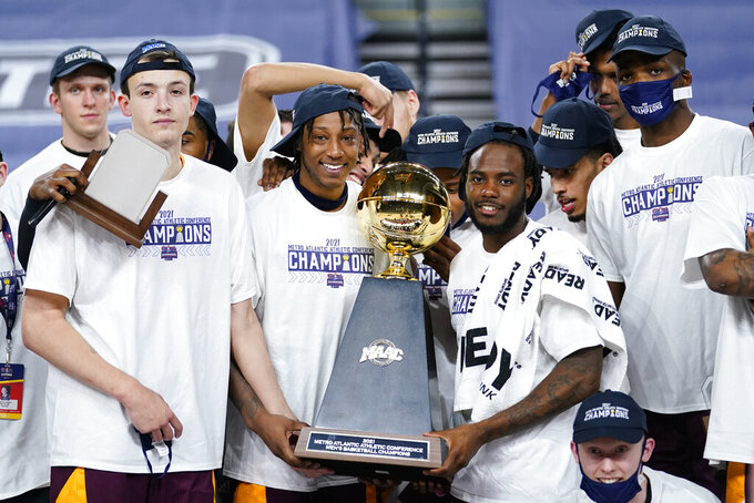 Iona players pose with the trophy after winning an NCAA college basketball game against Fairfield during the finals of the Metro Atlantic Athletic Conference tournament, Saturday, March 13, 2021, in Atlantic City, N.J. (AP Photo/Matt Slocum)