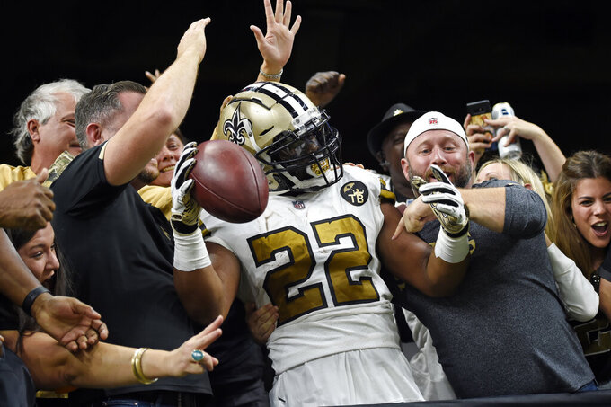 FILE - In this Nov. 18, 2018, file photo, New Orleans Saints running back Mark Ingram (22) celebrates his touchdown with fans after jumping into the stands in the first half of an NFL football game against the Philadelphia Eagles, in New Orleans. For the fans, team owners, sponsors and just about everyone else associated with college and professional sports, the coronavirus pandemic has forced changes both big and small. The most obvious change in the short term will be the implementation of social distancing. (AP Photo/Bill Feig, File)