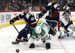 Dallas Stars center Justin Dowling, center, tumbles to the ice while pursuing the puck betwen Colorado Avalanche defenseman Samuel Girard, left, and center Pierre-Edouard Bellemare in the second period of an NHL hockey game Tuesday, Jan. 14, 2020, in Denver. (AP Photo/David Zalubowski)