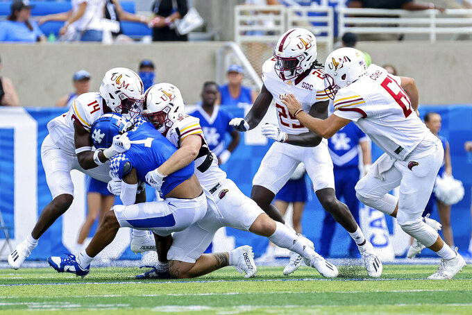 Kentucky wide receiver Wan'Dale Robinson (1) gets tackled by a host of Louisiana-Monroe defenders during the second half of an NCAA college football game in Lexington, Ky., Saturday, Sept. 4, 2021. (AP Photo/Michael Clubb)