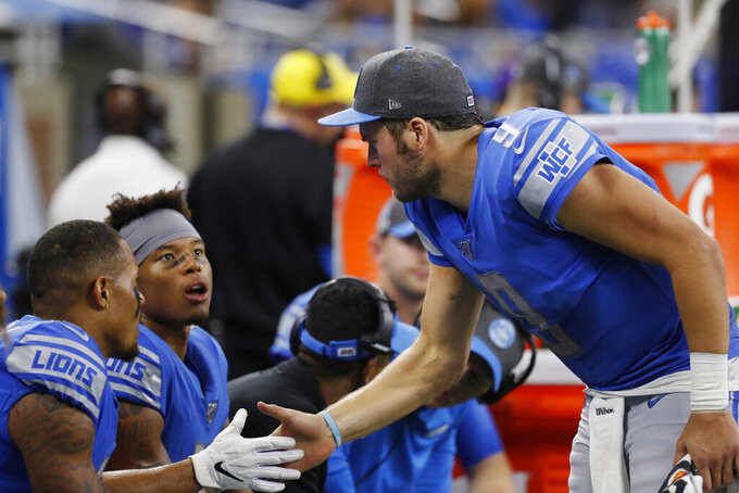 Detroit Lions quarterback Matthew Stafford, right, shakes hands with wide receiver Marvin Jones, second from left during the second half of an NFL football game against the Minnesota Vikings, Sunday, Oct. 20, 2019, in Detroit. Jones finished the game with four touchdowns. (AP Photo/Rick Osentoski)