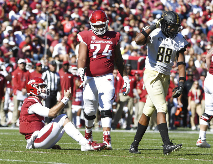 Arkansas quarterback Ty Storey gives Vanderbilt defender Michael Owusu the finger in the second half of an NCAA college football game Saturday, Oct. 27, 2018, in Fayetteville, Ark. Storey got upset when Owusu extended his hand to help him up only to pull it away when Storey reached out during Arkansas' 45-31 loss to Vanderbilt. (AP Photo/Michael Woods)