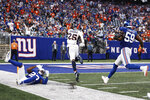 Denver Broncos running back Melvin Gordon (25) runs past New York Giants' Adoree' Jackson (22) and Lorenzo Carter (59) for a touchdown during the second half of an NFL football game Sunday, Sept. 12, 2021, in East Rutherford, N.J. The Broncos won 27-13. (AP Photo/Adam Hunger)