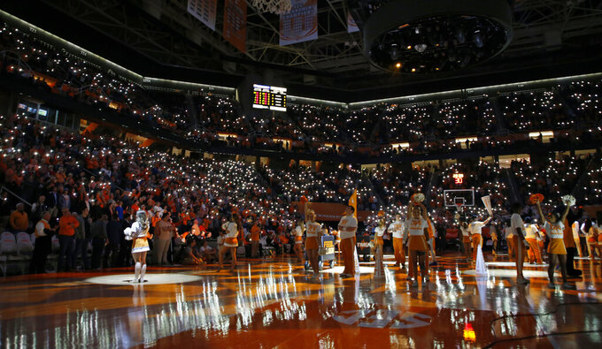 FILE - In this Feb. 19, 2019 file photo, fans hold up their cell phones with the flashlight on as music plays before an NCAA college basketball game between Tennessee and Vanderbilt in Knoxville, Tenn.  College basketball teams are trying to get fans to keep coming to games in the age of smartphones by making those phones an integral part of the experience. That's evident every time cellphones in the stands light up arenas across the country during pregame lineup introductions. (AP photo/Wade Payne, File)