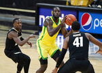 Oregon forward Eugene Omoruyi, center, drives between Colorado guard McKinley Wright IV, left, and forward Jeriah Horne in the first half of an NCAA college basketball game Thursday, Jan. 7, 2021, in Boulder, Colo. (AP Photo/David Zalubowski)