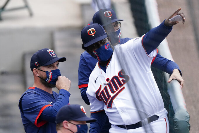 Minnesota Twins manager Rocco Baldelli, left, and first base coach Tommy Watkins speak in the dugout before the start of a spring training baseball game against the Boston Red Sox, Thursday, March 11, 2021, in Fort Myers, Fla.. (AP Photo/John Bazemore)