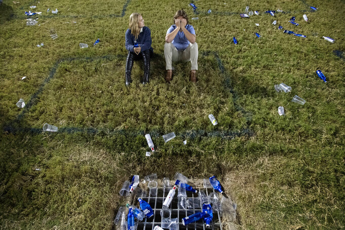 SMU sophomores Ashlyn Heintzelman and Peter Warner sit in a box marked on the grass to facilitate social distancing during the second half of an NCAA college football game between SMU and Cincinnati Saturday, Oct. 24, 2020, in Dallas. Cincinnati won 42-13. (AP Photo/Jeffrey McWhorter)