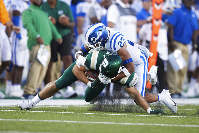 Charlotte tight end Ryan Carriere (85) is tackled by Duke safety Lummie Young IV (23) during the first half of an NCAA college football game Friday, Sept. 3, 2021, in Charlotte, N.C. (AP Photo/Brian Westerholt)