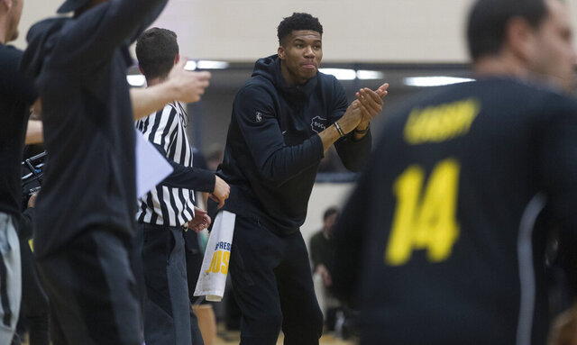 In this Tuesday, Dec. 17, 2019 photo, Milwaukee Bucks forward Giannis Antetokounmpo cheers on his team at the Racine Correctional Institution in Sturtevant, Wis. The Bucks were there as part of a program put on by the Anti-Recidivism Coalition, a group whose mission is to support incarcerated and formerly incarcerated people. Prior to the game there was a roundtable discussion among participants about topics such as criminal justice reform. (Mark Hoffman/Milwaukee Journal-Sentinel via AP)