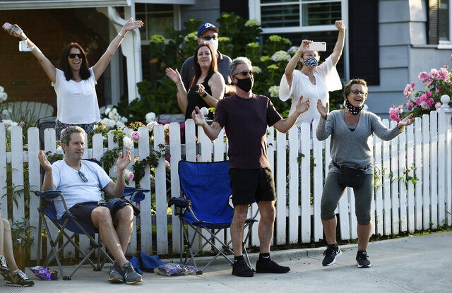 In this May 9, 2020 photo, SAG-AFTRA president Gabrielle Carteris, far right, and her husband Charles Isaacs, center, are among the cheering spectators at musician Adam Chester's weekly neighborhood performance in the Sherman Oaks section of Los Angeles. Normally, Chester is a surrogate Elton John, who sings and plays the rock superstar's parts at rehearsals. With that work on hold, Chester has been giving concerts to his neighbors from a safe social distance in front of his house. (AP Photo/Chris Pizzello)