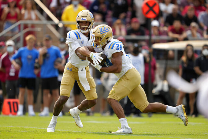 UCLA quarterback Dorian Thompson-Robinson (1) hands off to running back Zach Charbonnet (24) against Stanford during the first half of an NCAA college football game Saturday, Sept. 25, 2021, in San Francisco, Calif. (AP Photo/Tony Avelar)