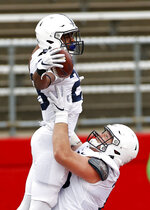 Penn State running back Devyn Ford is congratulated by offensive lineman Mike Miranda, right, after scoring a touchdown during the first half of an NCAA college football game against Rutgers on Saturday, Dec. 5, 2020, in Piscataway, N.J. (AP Photo/Adam Hunger)