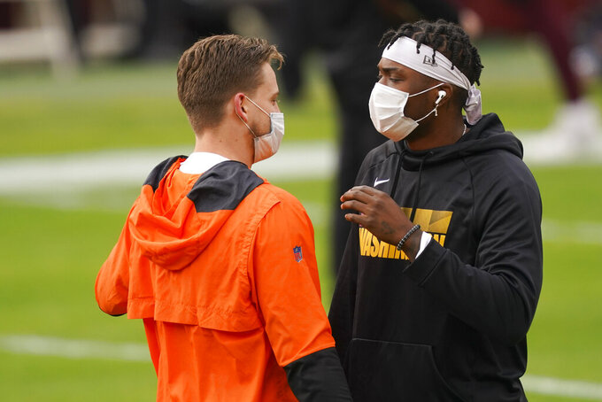 Cincinnati Bengals quarterback Joe Burrow, left, and Washington Football Team quarterback Dwayne Haskins, right, talk to one another on the field during pregame warm-ups before the start of an NFL football game Sunday, Nov. 22, 2020, in Landover, Md. (AP Photo/Andrew Harnik)