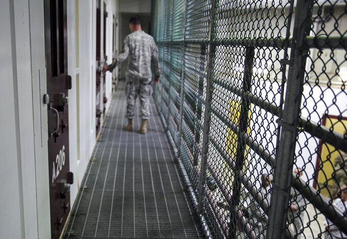 FILE - In this Feb. 6, 2016, file photo, an Army captain walks outside unoccupied detainee cells inside Camp 6 at the U.S. detention center at Guantanamo Bay, Cuba. The White House says it intends to shutter the prison on the U.S. base in Cuba, which opened in January 2002 and where most of the 39 men still held have never been charged with a crime. (AP Photo/Ben Fox, File)