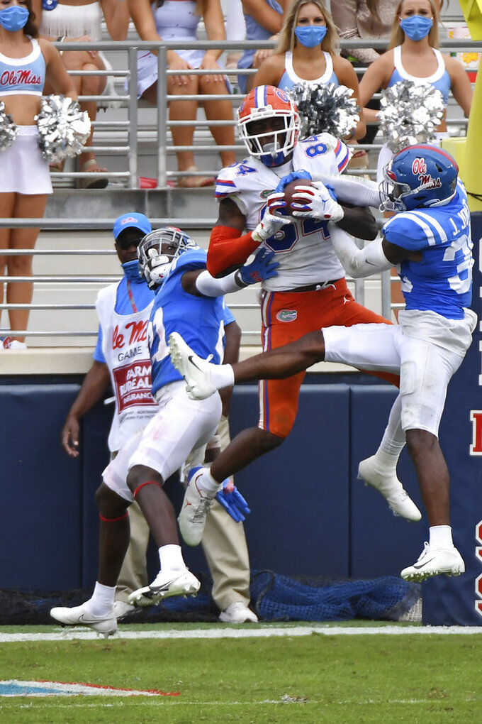 Florida tight end Kyle Pitts (84) catches touchdown pass over Mississippi defensive backs A.J. Finley (21) and Jaylon Jones (38) during the second half of an NCAA college football game in Oxford, Miss., Saturday, Sept. 26, 2020. No. 5 Florida won 51-35. (AP Photo/Thomas Graning)