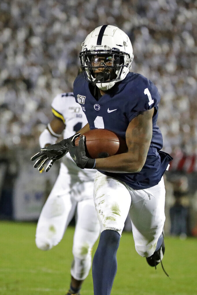 Penn State wide receiver KJ Hamler (1) scores after catching a pass from quarterback Sean Clifford during the second half of the team's NCAA college football game against Michigan in State College, Pa., Saturday, Oct. 19, 2019. Penn State won 28-21. (AP Photo/Gene J. Puskar)