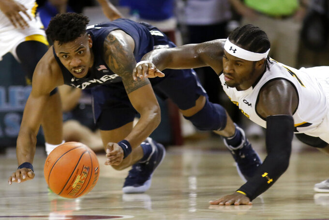 Xavier's Paul Scruggs, left, and Towson's Jakigh Dottin dive for the ball during the first half of an NCAA college basketball game during the Charleston Classic on Thursday, Nov. 21, 2019, in Charleston, SC. (AP Photo/Mic Smith)