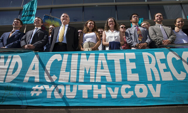 FILE - In this July 18, 2018, file photo, lawyers and youth plaintiffs lineup behind a banner after a hearing before Federal District Court Judge Ann Aiken between lawyers for the Trump Administration and the so called Climate Kids in Federal Court in Eugene, Ore. A federal appeals court on Friday, Jan. 17, 2020, dismissed a lawsuit by 21 young people who claimed the U.S. government's climate policy harms them and jeopardizes their future. (Chris Pietsch/The Register-Guard via AP, File)