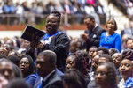 Mourners stand and clap as music plays during the memorial service for slain Lowndes County Sheriff John Williams, Monday, Dec. 2, 2019, in Montgomery, Ala. (AP Photo/Vasha Hunt)