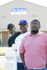 Richard Strong, 50, left, his brother Gregory Strong, 48, center and Stacy Griffin, 42, right, stand across the road from Pitts Chemical offices in Indianola, Miss., Thursday, Sept. 9, 2021. The three are among six Black farmworkers in Mississippi who say in a new lawsuit that their former employer, Pitts Farm Partnership, has brought white laborers from South Africa to do the same jobs they were doing, and that the farm has been violating federal law by paying the white immigrants significantly more for the same type of work. (AP Photo/Rogelio V. Solis)