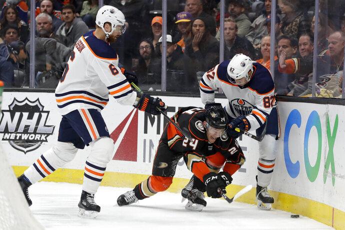 Anaheim Ducks center Carter Rowney goes after the puck between Edmonton Oilers defenseman Adam Larsson, left, and defenseman Caleb Jones during the second period of an NHL hockey game in Anaheim, Calif., Tuesday, Feb. 25, 2020. (AP Photo/Chris Carlson)