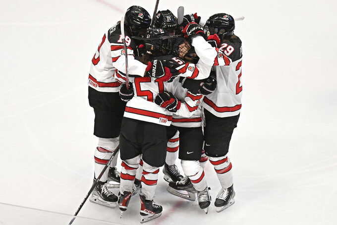 Teammates celebrate with Canada's Victoria Bach after her goal against the United States in the first period of a women's hockey game in a pre-Olympic Games series Monday, Oct. 25, 2021, in Hartford, Conn. (AP Photo/Jessica Hill)