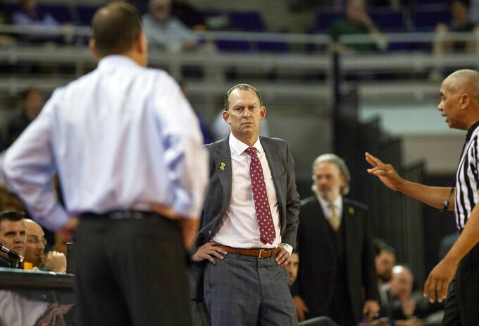 East Carolina head coach Joe Dooley, middle, stares in the direction of Houston Head Coach Kelvin Sampson, left, moments before Dooley was ejected from an NCAA college basketball game in Greenville, N.C., Wednesday, Feb. 27, 2019. (AP Photo/Ben McKeown)