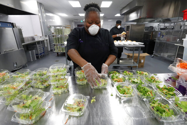 Chef Rose Barrett prepares dinner salads that would accompany the chicken tetrazzini being made by the staff in the commercial kitchen at The Potters House Church in Dallas, Friday, March 27, 2020. The church's kitchen staff planned on making and donating 1,000 meals that would be delivered to area healthcare workers and first responders as they help in the fight against the coronavirus outbreak. The kitchen which is part of the church founded by Bishop T.D. Jakes, typically prepares meals for banquets, high school graduations and community functions being held at the church's event center. (AP Photo/Tony Gutierrez)