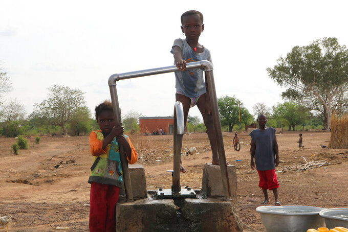 Children play on a water pump in an internally displaced camp in Gaoa, Burkina Faso, April 22, 2021. Until recently life was peaceful in western Burkina Faso's Comoe province, but an increase in attacks by extremist groups in the country's west has put the military on edge. Burkina Faso is experiencing an increase in extremist violence by groups linked to al-Qaida and the Islamic State.(AP Photo/Sam Mednick)