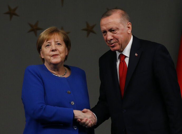 Germany's Chancellor Angela Merkel, left, shakes hands wit Turkey's President Recep Tayyip Erdogan, right, following their joint news conference after their meeting in Istanbul, Friday, Jan. 24, 2020. Merkel met Erdogan for talks that are expected to focus on the future of a migration deal between Turkey and the EU that helped decrease refugee flows to Europe.(AP Photo/Emrah Gurel)