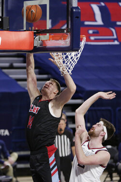 Loyola Marymount center Mattias Markusson, left, shoots in front of Gonzaga forward Drew Timme during the first half of an NCAA college basketball game in Spokane, Wash., Saturday, Feb. 27, 2021. (AP Photo/Young Kwak)