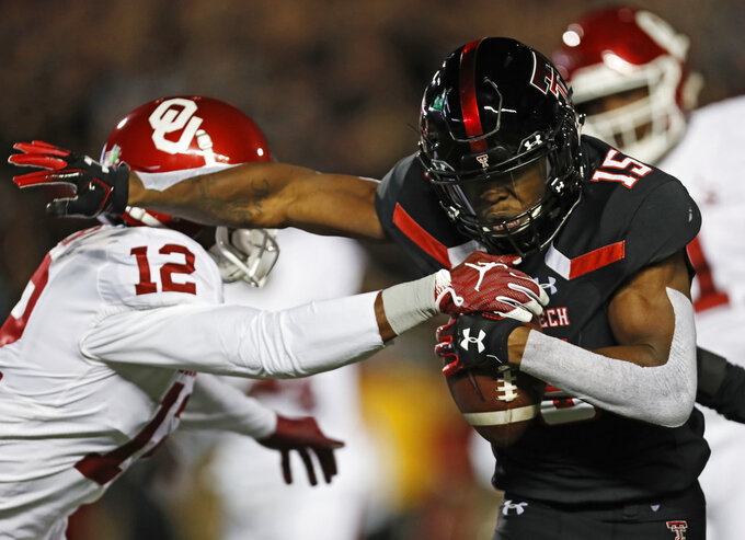 Texas Tech's Vaughnte Dorsey (15) breaks a tackle by Oklahoma's A.D. Miller (12) after intercepting a pass during the first half of an NCAA college football game Saturday, Nov. 3, 2018, in Lubbock, Texas. (AP Photo/Brad Tollefson)