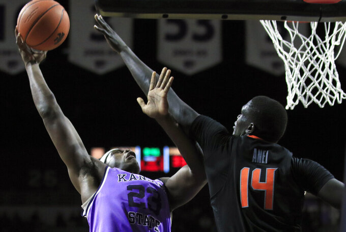 Kansas State forward Austin Trice (23) shoots over Oklahoma State forward Yor Anei (14) during the second half of an NCAA college basketball game in Manhattan, Kan., Saturday, Feb. 23, 2019. (AP Photo/Orlin Wagner)