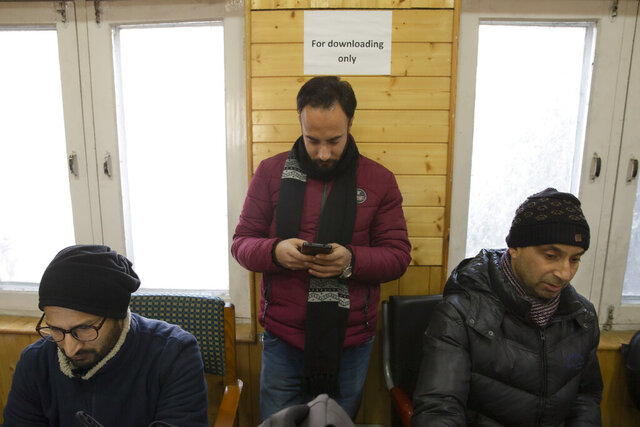 In this Jan. 30, 2020, photo, a Kashmiri journalist, center, browses the internet on his mobile phone inside the media center set up by government authorities in Srinagar, Indian controlled Kashmir. Six months after India stripped restive Kashmir of its semi-autonomy, enforcing a total communications blackout, it has restored limited internet at slow speeds with access only to government-approved websites. Since Modi came into power in 2014, the internet has been suspended more than 365 times in India, according to the global digital rights group Access Now. (AP Photo/ Dar Yasin)