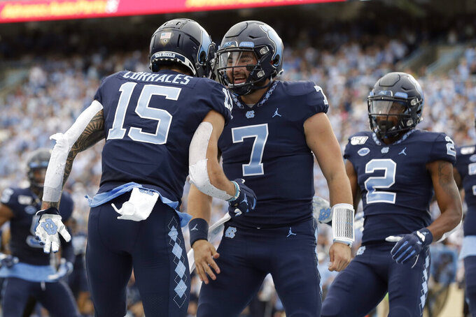 North Carolina quarterback Sam Howell (7) and wide receiver Beau Corrales (15) celebrate a touchdown against Duke during the first half of an NCAA college football game in Chapel Hill, N.C., Saturday, Oct. 26, 2019. (AP Photo/Gerry Broome)