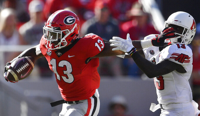Georgia running back Elijah Holyfield (13) runs by Austin Peay defensive back Kordell Jackson (13) during the second half of an NCAA college football game, Saturday, Sept. 1, 2018, in Athens, Ga. (AP Photo/Mike Stewart)