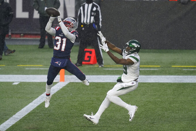 New England Patriots defensive back Jonathan Jones, left intercepts a pass in the end zone intended for New York Jets wide receiver Breshad Perriman, right, in the second half of an NFL football game, Sunday, Jan. 3, 2021, in Foxborough, Mass. (AP Photo/Elise Amendola)