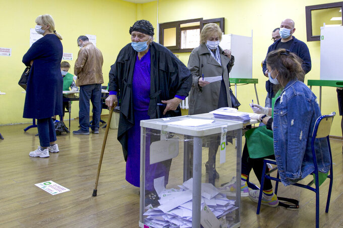 Georgians wearing face masks to help curb the spread of the coronavirus, cast their ballots at a polling station during the parliamentary elections in Tbilisi, Georgia, Saturday, Oct. 31, 2020.  The hotly contested election between the Georgian Dream party, created by billionaire Bidzina Ivanishvili who made his fortune in Russia and has held a strong majority in parliament for eight years, and an alliance around the country's ex-president who is in self-imposed exile in Ukraine.  (AP Photo/Shakh Aivazov)