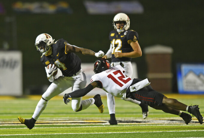 Appalachian State running back Daetrich Harrington, left, tries to get around Arkansas State linebacker C.J. Harris (12) in the first half of an NCAA college football game, Thursday, Oct. 22, 2020, at Kidd Brewer Stadium in Boone, N.C. (Walt Unks/Winston-Salem Journal via AP)