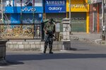 A paramilitary soldier stands guard outside a closed market area in Srinagar, Indian controlled Kashmir, Thursday, Sept. 2, 2021. Syed Ali Geelani, a top separatist leader and one of the severest critics of Indian rule in the disputed Himalayan region of Kashmir, died late Wednesday. He was 92. Authorities announced a communication blockade and the restriction of public movement, a common tactic employed by Indian officials in anticipation of anti-India protests. (AP Photo/Dar Yasin)