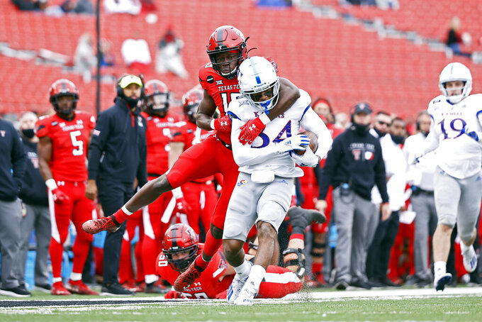 Texas Tech's Loic Fouonji (19) tackles Kansas' Nate Betts (34) after he recovered a fumble by Texas Tech during the second half of an NCAA college football game Saturday, Dec. 5, 2020, in Lubbock, Texas. (AP Photo/Brad Tollefson)