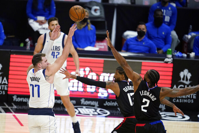 Dallas Mavericks guard Luka Doncic (77) shoots over Los Angeles Clippers guard Paul George, center, and forward Kawhi Leonard (2) during the first half in Game 2 of an NBA basketball first-round playoff series Tuesday, May 25, 2021, in Los Angeles. (AP Photo/Marcio Jose Sanchez)