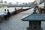 A man and a woman wearing face masks watch the Sumida River as they visit its riverside walking trail in Tokyo, Thursday, Sept. 16, 2021. (AP Photo/Hiro Komae)