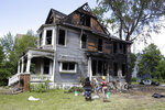 Workers clean up a duplex in the 2100 block of north 40th that was set on fire, following an incident Tuesday, where three people had been shot, Thursday, June 25, 2020, in Milwaukee. Two missing teenage girls were never at the Milwaukee house that was set on fire during unrest that saw three people shot and 10 police officers and a firefighter injured as a large unruly crowd gathered at the scene of the investigation, police said Wednesday. (Rick Wood/Milwaukee Journal-Sentinel via AP)