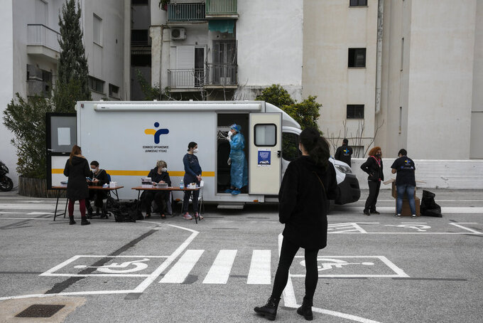 People wait to get tested for COVID-19, at a National Health Organisation (EODY) outdoor testing point, in Athens, Sunday, March 14, 2021. More than 1.1 million doses of the COVID-19 vaccine have been administered so far in Greece, but infections remain on the rise despite four months of lockdown measures. (AP Photo/Yorgos Karahalis)
