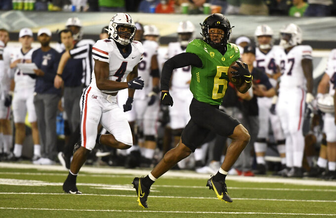 Oregon wide receiver Jaylon Redd (6) looks back as he is pursued by Arizona cornerback Christian Roland-Wallace (4) while heading to the end zone on a 75-yard run in the first quarter of an NCAA college football game Saturday, Sept. 25, 2021, in Eugene, Ore. (AP Photo/Andy Nelson)