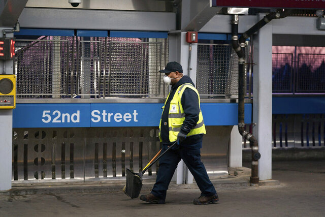 FILE- In this March 18, 2020 file photo, SEPTA worker Ervin Lavenhouse wears a mask as he works sweeping up trash on the platform at the 52nd Street station, in Philadelphia. The Transport Workers Union that represents nearly 5,000 employees of Philadelphia's regional mass transit authority wants the Southeastern Pennsylvania Transportation Authority to remove a cap on paid leave if workers are exposed to coronavirus.  (Jessica Griffin/The Philadelphia Inquirer via AP, File)